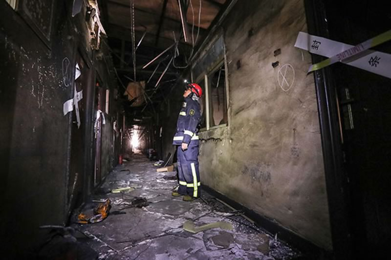 Firefighters inspect the burnt out Gathering Good Fortune Building in Daxing